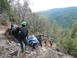PHOTO BY RYAN BURNS - A crew of volunteers descends a hill near the Humboldt-Trinity County border while Army National Guard soldiers help coordinate.