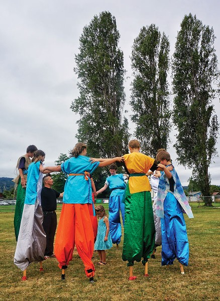A group of young stilt walkers from the Arcata Playhouse Pageant on the Plaza workshop forms a circle before performing a play, The Battle of the Elements, at Annie and Mary Days on Sunday, July 13, at Perigot Park in Blue Lake. (The pageant was also presented on Saturday on the Arcata Plaza.) - PHOTO BY BOB DORAN