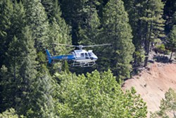 PHOTO BY PRESTON DRAKE-HILLYARD - A helicopter searches for Sophia Pedreros-Parker Saturday, May 21