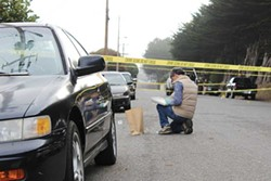 "PHOTO BY THADEUS GREENSON - A member of the multiagency Humboldt County Critical Incident Response Team collects evidence on Allard Street, where a Eureka police officer shot and killed Thomas ""Tommy"" McClain on Sept. 17, 2014."