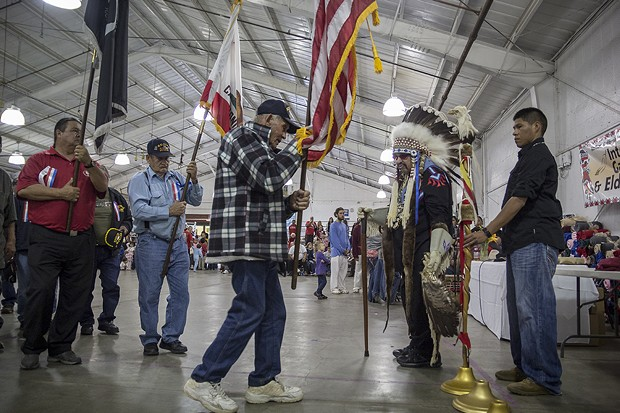 An elder veteran carries an American flag during the part of the ceremony honoring veterans. - MANUEL J. ORBEGOZO
