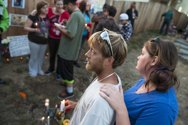 """Andrew Evans holds a candle during the vigil for his friend and co-worker. Evans said McClain's death was mind blowing adding, """"He was a mellow, kind kid. I could never see him being violent."""" - MARK MCKENNA"""