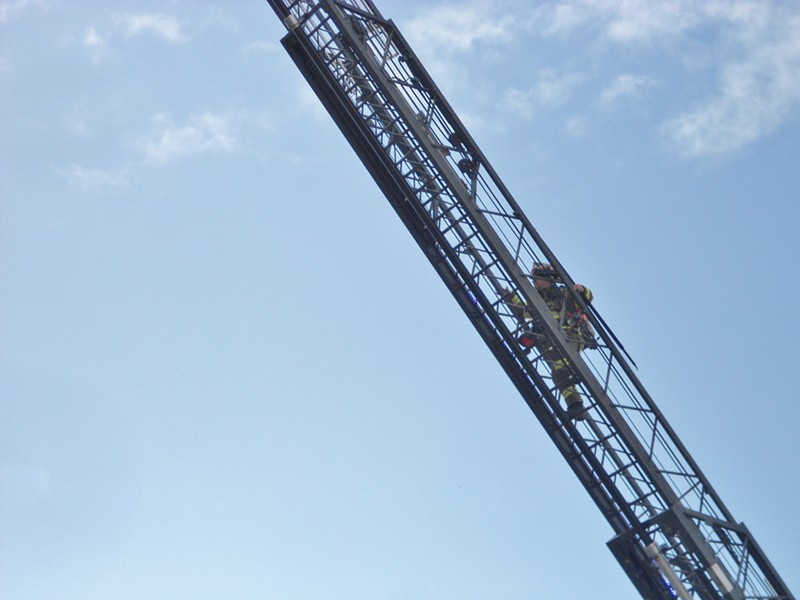 A firefighter climbs the ladder. - LINDA STANSBERRY
