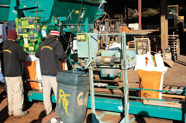 As orange plastic bags puff full with soil, Royal Gold workers pull them away from a hopper, put them on a conveyor belt, and send them to a machine that seals each bag with a hiss. - PHOTO BY ZACH ST. GEORGE