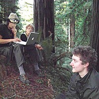 "What Now, Treesitter? At a recent gathering at the Nanning Creek treesit, Lodgepole, at the computer, shows long-time forest activist Naomi Wagner a treesit video he made. ""Cedar,"" who has lived almost 11 months in a tree, has just descended. Photo by Heidi Walters"