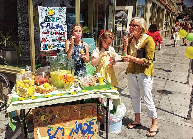 Ava Berg, Naia Ryman and Ava's grandmother, Siv Berg, blow bubbles to attract customers to their Lemonade Day booth in front of Arcata's Garden Gate on Saturday, June 7. - PHOTO BY BOB DORAN