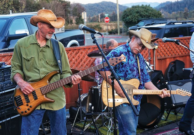 Bassist Ron Sharp and lead guitarist Rick Levin of the cosmic American music band Cadillac Ranch trade licks at a dance concert at Mad River Brewery in Blue Lake on a warm summer Friday evening, Aug. 15. - PHOTO BY BOB DORAN