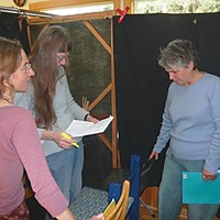 Dr. Ring's Single-Payer Puppet Show Behind the scenes Susan Brinton (right) and other cast members rehearse backstage. Photo by Hank Sims