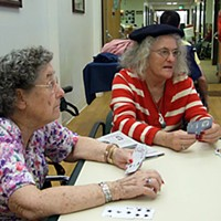 "'Immediate Jeopardy' Betty Hansen (left) and Sue Prime play cards at St. Luke. Hansen said they keep them busy at St. Luke with trips to the movies, zoo and Table Bluff. As for the meals:  ""One's good and another's horrible.""  Photo by Carol Harrison"