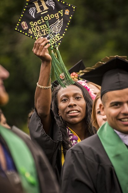 Brejeque Collins, sociology major and HSU student athlete in the womens 400-meter run, held her inscribed hat aloft as she exited the Redwood Bowl field following commencement. - MARK LARSON