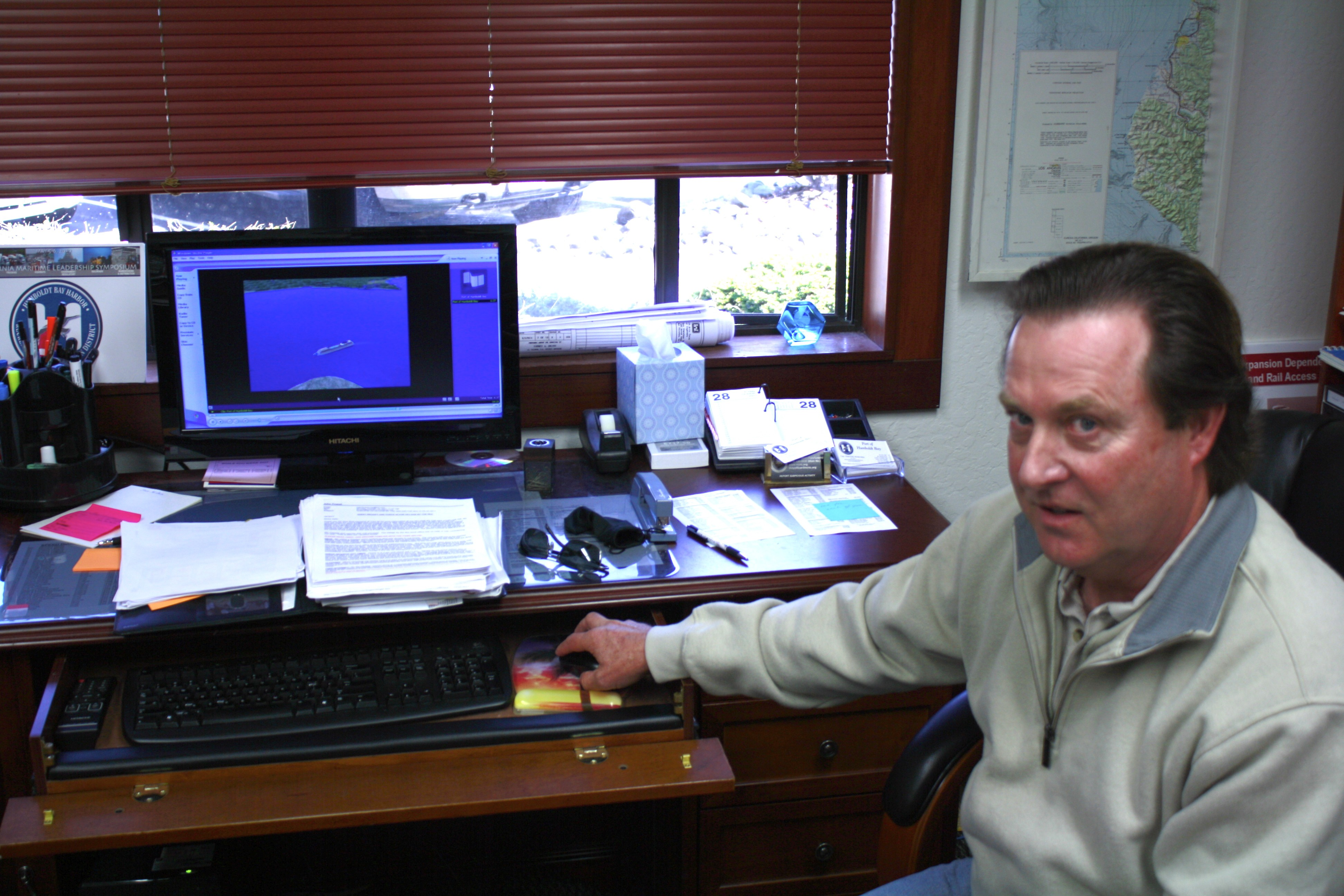 Captain John Powell spends more time than he'd like his desk. His computer is running an educational simulation he helped create, of a ship entering Humboldt Bay. - PHOTO BY ZACH ST. GEORGE