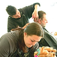 "Everyone Is Connected Courtney Voth, a student at Fredrick and Charles Beauty College, giving a free haircut. ""A lot of young women have been wanting layered haircuts,"" says the college's owner, Jeanie Scott. Photo by David Lawlor"