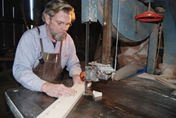 PHOTO COURTESY OF BLUE OX MILLWORKS - Craftsman Eric Hollenbeck, of Blue Ox Millworks, cutting an upper trim detail.
