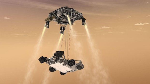 """Curiosity's """"sky crane"""" system. The spacecraft's descent stage lowers the rover on a bridle prior to touchdown in Gale Crater, five degrees south of the Martian equator. - COURTESY OF NASA"""