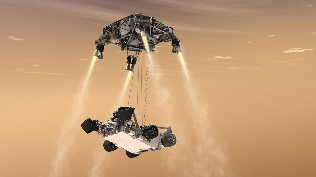 "Curiosity's ""sky crane"" system. The spacecraft's descent stage lowers the rover on a bridle prior to touchdown in Gale Crater, five degrees south of the Martian equator. - COURTESY OF NASA"