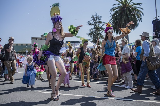 """Dancers with little """"fruit flies"""" behind them participating in the Samba parade at the North County Fair. - ALEXANDER WOODARD"""