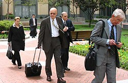 Defense attorney James Brosnahan (center, bald) and MAXXAM Chief Charles Hurwitz (behind Brosnahan) leave the Oakland Federal Courthouse Monday, which turned out to be the last day of the trial.  Photo by John Geluardi