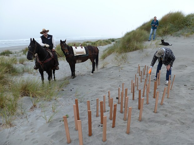 Dennis Mayo of McKinleyville sits horseback while Ray Reel of Manila pounds wooden stakes into the sand.