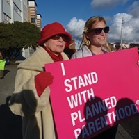 Ellen Bryant (left) and Beth Werner were among an estimated 200 persons who turned out at the behest of Six Rivers Planned Parenthood to protest budget cuts that could trim funds representing about 3.5 percent of the organization's total budget