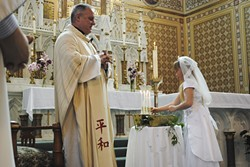 PHOTO COURTESY OF ST. BERNARD PARISH - Father Eric Freed at First Communion, 2013