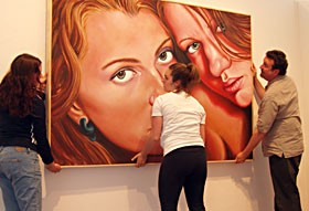 "First Street Gallery student assistants Camille Zazou and Erica Botkin work with gallery director Jack Bentley hanging a oil painting by Tom Harley titled, ""Post Beauty"" for the Young Alumni 2007 show opening this weekend."