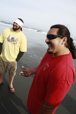 PHOTOS BY ZACH ST. GEORGE - Frankie Myers holds a clam while his brother R.L. Myers looks on. Craig Tucker caught the clam – he's not part of any tribe, and he was happy to show his fishing license.