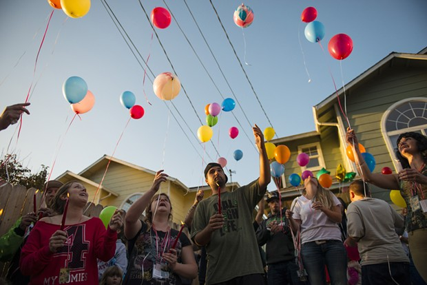 """Friends and family release balloons during a vigil for Thomas """"Tommy"""" McClain held at the scene of Wednesday's shooting. - MARK MCKENNA"""