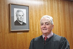 PHOTO BY THADEUS GREENSON - Humboldt County Superior Court Judge W. Bruce Watson stands in front of a portrait of his father, the late Judge William Watson Jr. Watson has announced that he will retire in January, after 23 years on the Humboldt County bench.