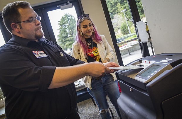 Clerk Jesse Hoskins casts a ballot into a voting machine at the Humboldt State University polling station. - MANUEL J. ORBEGOZO