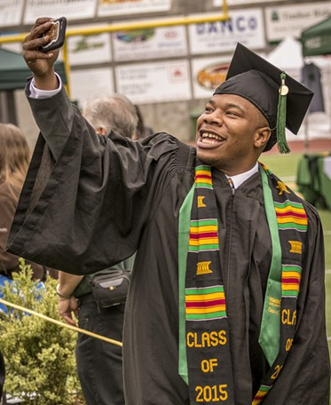 Journalism major Anthony Johnson takes a selfie as the 2015 candidates for graduation enter Redwood Bowl. - MARK LARSON
