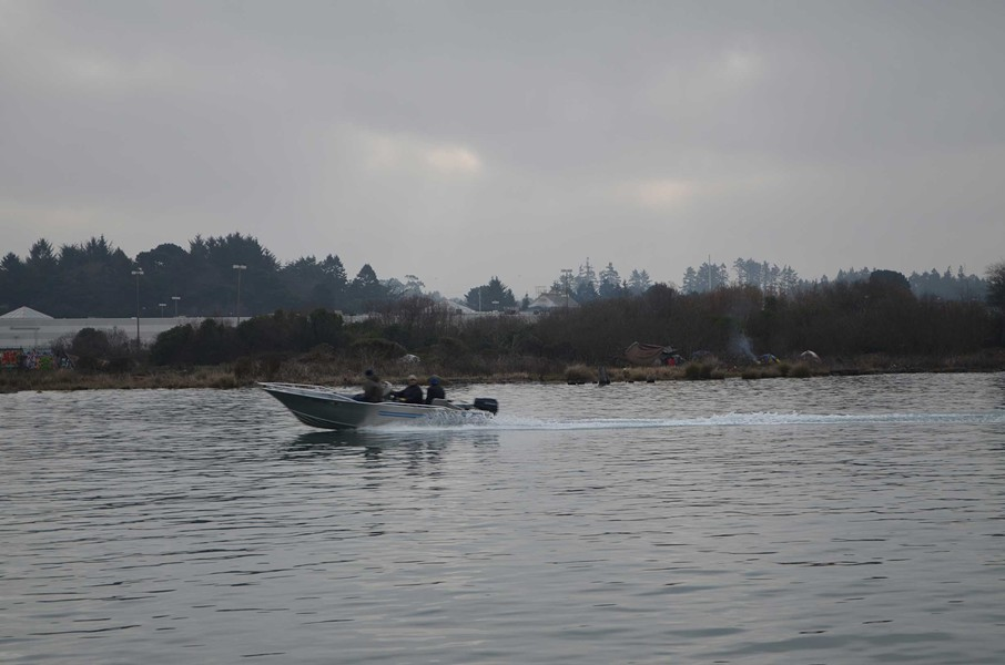 A boat zips by homeless encampments on the bay side of the Bayshore Mall. - GRANT SCOTT-GOFORTH