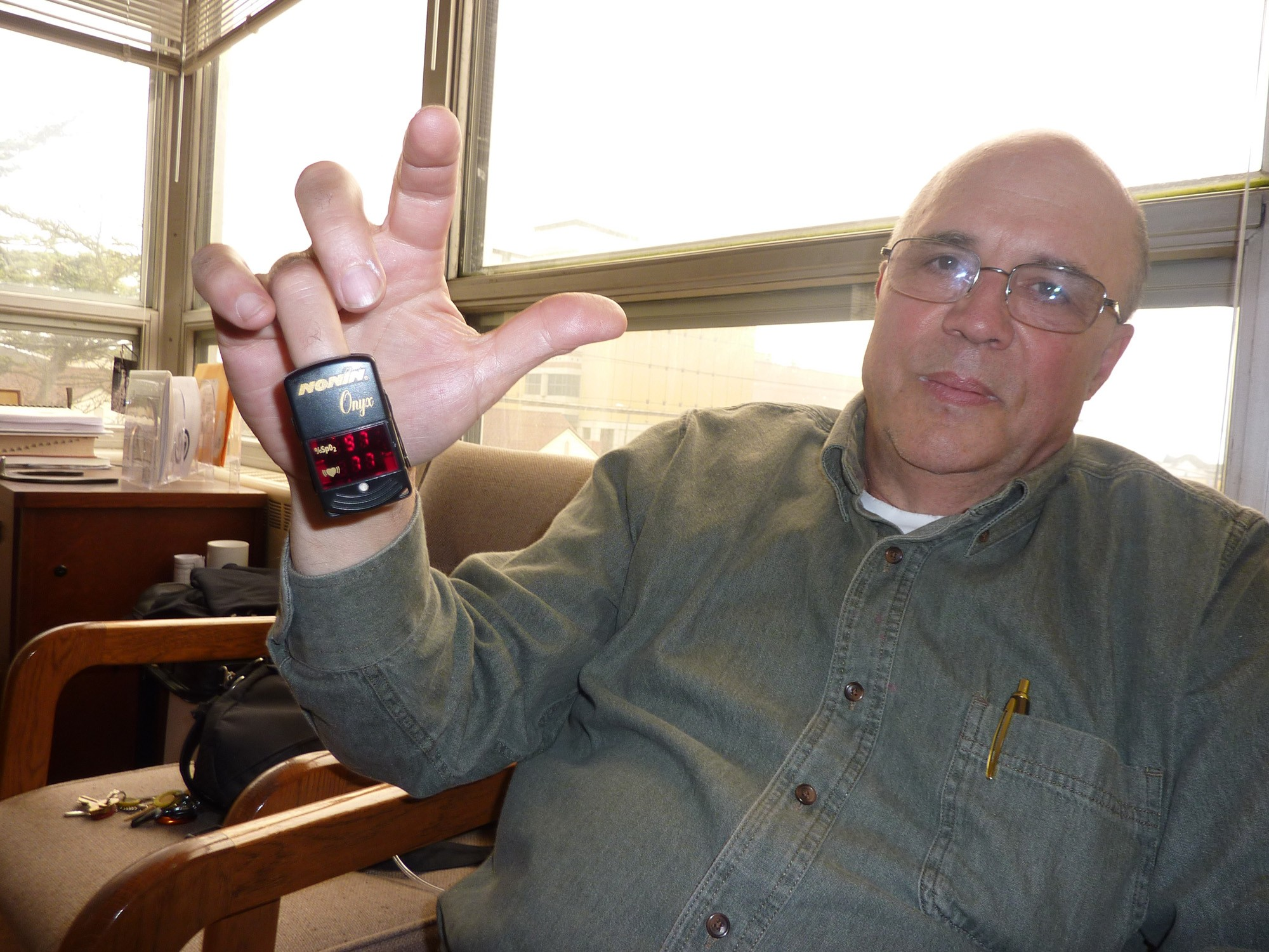 Lance Madsen displays his oximeter, which measures his pulse and blood oxygen. - PHOTO BY RYAN BURNS