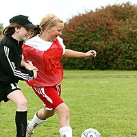 Soccer Dreams Maddie Moore and Faith Long (in black) chasing down a 50-50 ball. Photo by Bob Doran