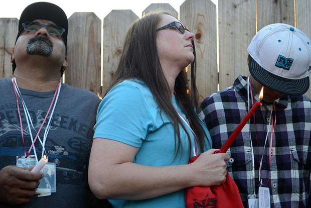 McClain's stepfather, Frank Barragan, left, his mother Jeanne, and brother, Nathaniel, comfort each other shortly after friends and family released balloons during Friday's Vigil. - MARK MCKENNA