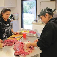 Klamath: Direct Action! Molli White, left, and Annelia Hillman prepare elk meat for the Klamath Justice Coalition dinner. Photo by Malcolm Terence.