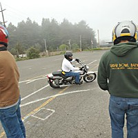 Keep Upright! Motorcycle Training instructor Rico Garcia demonstrates the proper negotiation of a curve to students of the motorcycle safety course at the Redwood Acres parking lot in Eureka.  Photo by Mark McKenna