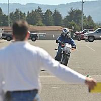 Keep Upright! Motorcycle Training instructor Rico Garcia uses hand signals to tell student Jeff Skehen to simulate a left lane change. Photo by Mark McKenna