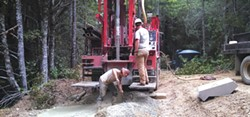 PHOTO BY DAVE FISCH. - Nate Ohlsson runs the drill and Andy Neuman shovels cuttings on well-drilling job for Fisch Drilling.