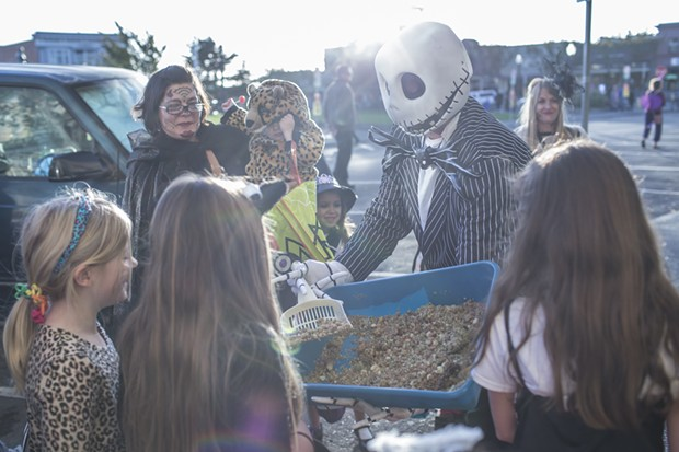 Kevi from Panache, passes out 'kitty litter cake' to trick-or-treaters on the plaza Friday. - ALEXANDER WOODARD