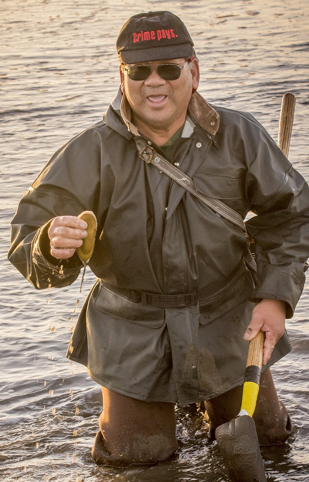 """James Louis, of Eureka, said he's known as the """"black belt clammer"""" after 45 years of successfully pursuing razor clams on Clam Beach. He held up one example of the tasty clam after going to his knees to dig it out on a low tide just before sunset on Tuesday, Jan. 20. - MARK LARSON"""