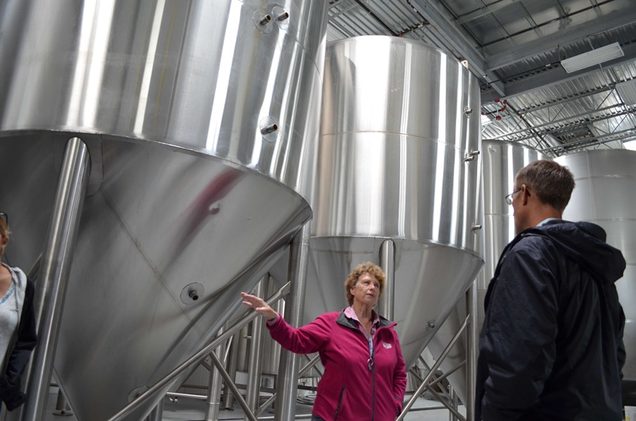 Groom shows off the brewery's fermentation tanks. - GRANT SCOTT-GOFORTH