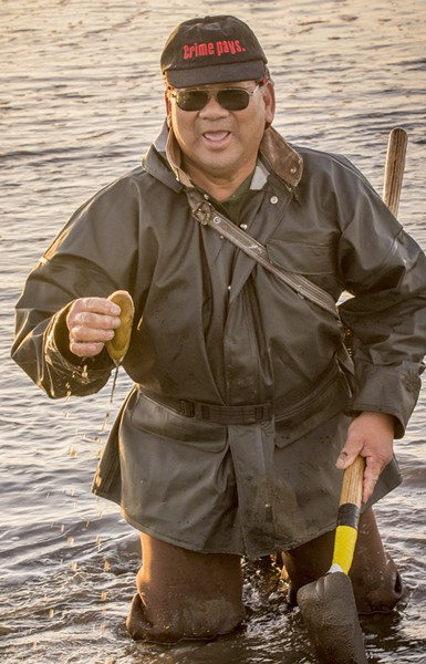 "James Louis, of Eureka, said he's known as the ""black belt clammer"" after 45 years of successfully pursuing razor clams on Clam Beach. He held up one example of the tasty clam after going to his knees to dig it out on a low tide just before sunset on Tuesday, Jan. 20. - MARK LARSON"