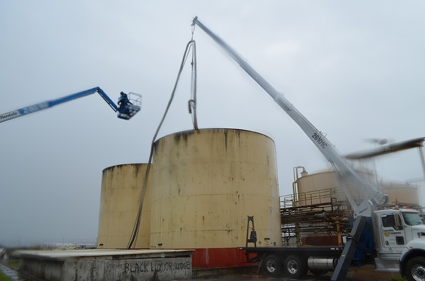 Workers lower a pump into one of the liquor tanks. - GRANT SCOTT-GOFORTH