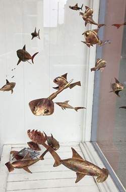 "PHOTO BY CARRIE PEYTON DAHLBERG - One of the few sharks that will make you go ""squeee"" swims among a window full of copper sea creatures. The Scott Hemphill creations decorate the offices of Humboldt Baykeeper for this month's Arts Alive. (And the ray is pretty adorable, too.)"