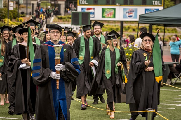 Professor Noah Zerbe, Department of Politics, served as the mace bearer and professors Cindy Moyer, Music, and Sarah Wharf, Art, followed in their role as marshalls as they led the graduate and undergraduate students into Redwood Bowl. - MARK LARSON
