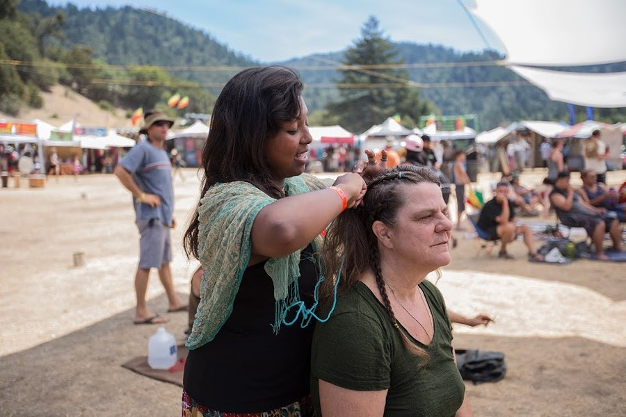 "Jerusha Westlake works as a vendor braiding hair for her and her mother's business ""Braids With Love"" at the 30th annual Reggae On The River 2014, Friday Aug. 1. - ALEXANDER WOODARD"
