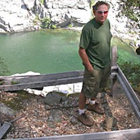 "Rock and a Hard Place — Independent gold miners fear extinction as a new wave hits the hills Richard Cormier stands in the remains of his outdoor ""miner's bed"" at his former claim on the salmon river.  Photo by Heidi Walters"