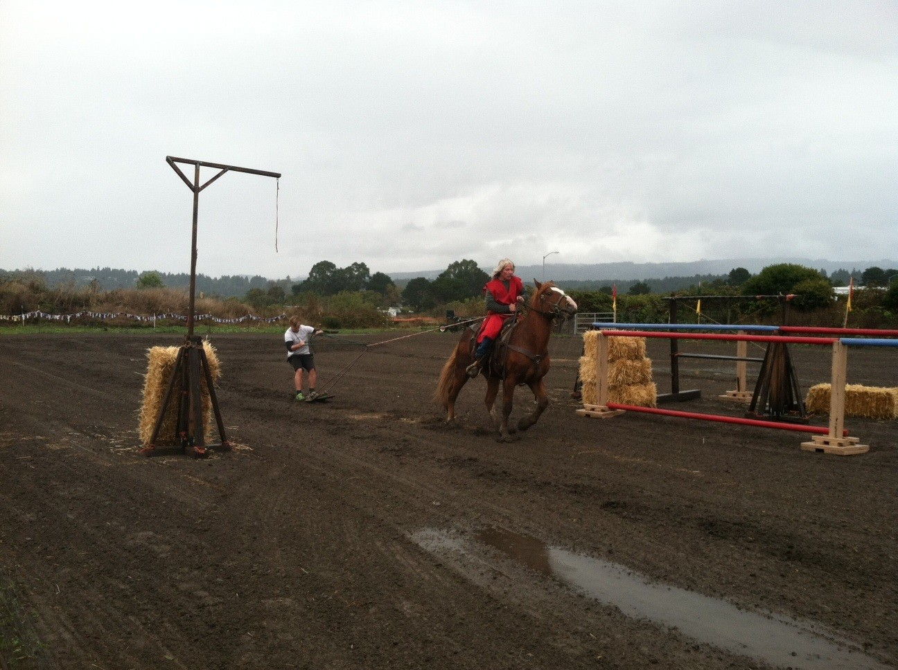 Ridin' dirty. A mud-skier hitches a ride behind a jouster. - TONY SMITHERS