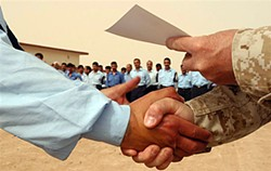 Right rules! A newly-graduated Iraqi policeman gets a congratulatory right-handshake from a U.S. Marine commandant while receiving his certificate with the left hand. Cpl. Paula Fitzgerald, Public Domain