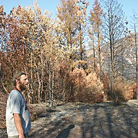 Our Fire, Our Fight Ryan Wiegel walks through the aftermath two months after the fires. The scorched slope of East Peak is in the background. Photo by Malcolm Terence